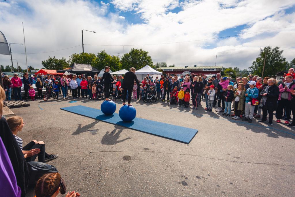 Nuoret sirkustaiteilijat tasapainoilevat pallojen päällä ja runsaasti yleisöä seuraa esitystä KesäKolari2018 -tapahtumassa.