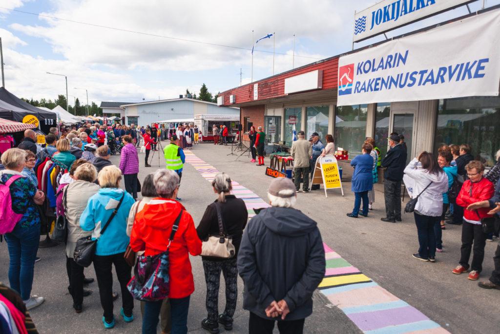 Kuvassa on seisomassa olevia KulttuuriKolari 2018 -tapahtuman osallistujia, jotka seuraavat ohjelmanumeroa. Kuva on otettu Jokijalka 65:n edessä ulkona ja siinä on ihmisten lisäksi toritelttoja ja rakennusta.