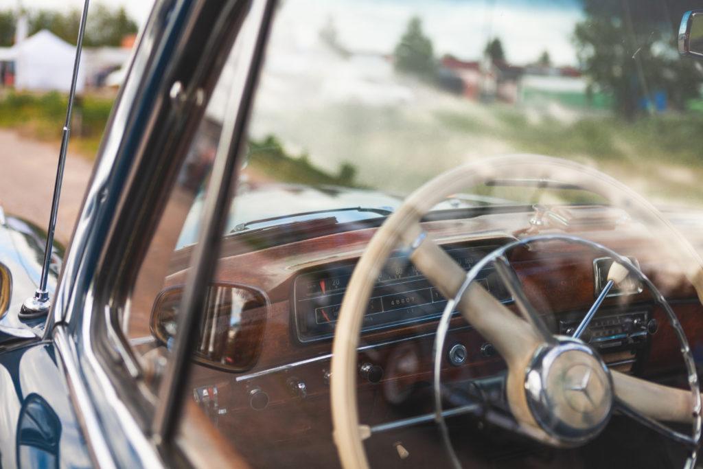 Taidekuva, joka on otettu auton ulkopuolelta. Amerikan rauta-autosta näkyy lasin läpi rattia.