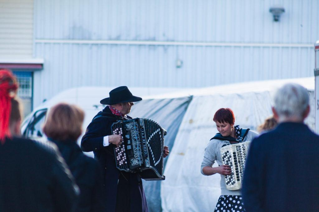 Mies ja nainen soittavat ulkona hanuria tapahtumassa.