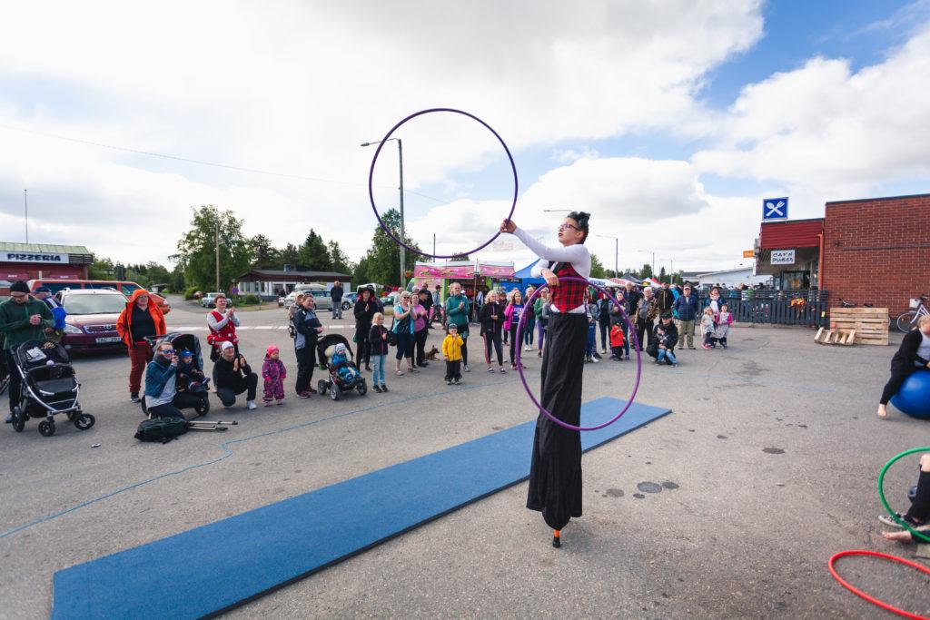 Nuori tyttö tekee sirkustemppuja puujaloilla kävellen ja hulahula-vanteita heiluttaen käsissään. Kuva otettu tytön takaa. Katsojat ottavat esiyksestä kuvia.