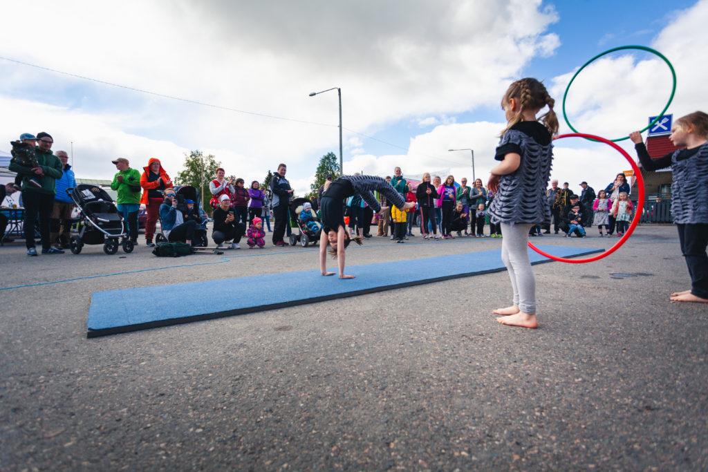 Nuori tyttö seisoo käsillään yleisön edessä ulkona KulttuuriKolari 2018 -tapahtumassa.