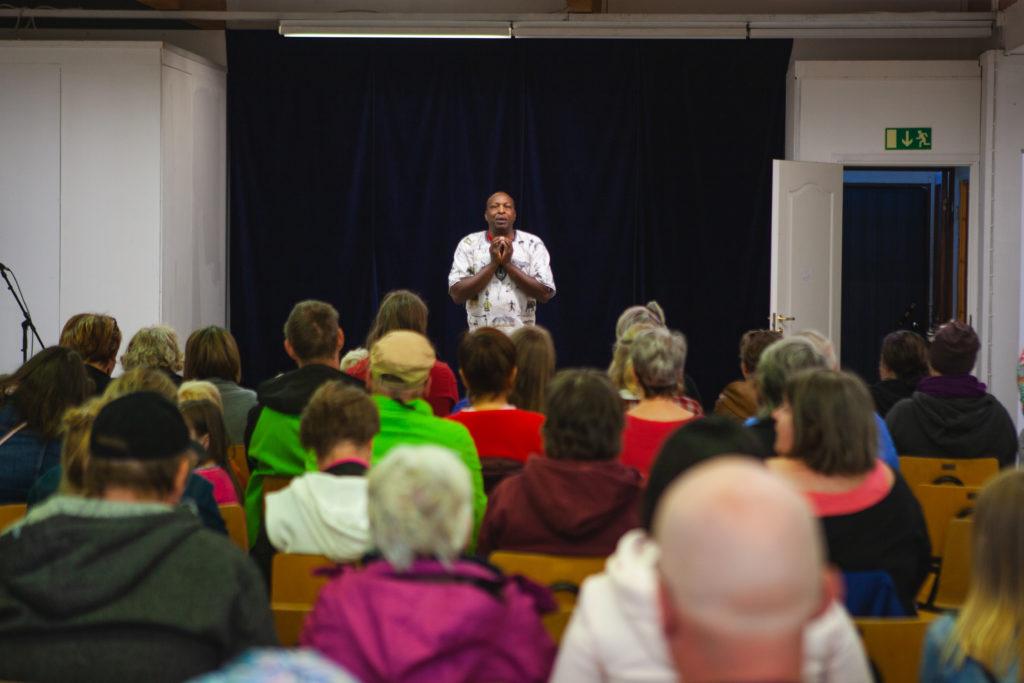 Yleisö kuuntelee istuen edessä puhuvaa Wilson Kirwaa, joka on tunnettu pikajuoksia.