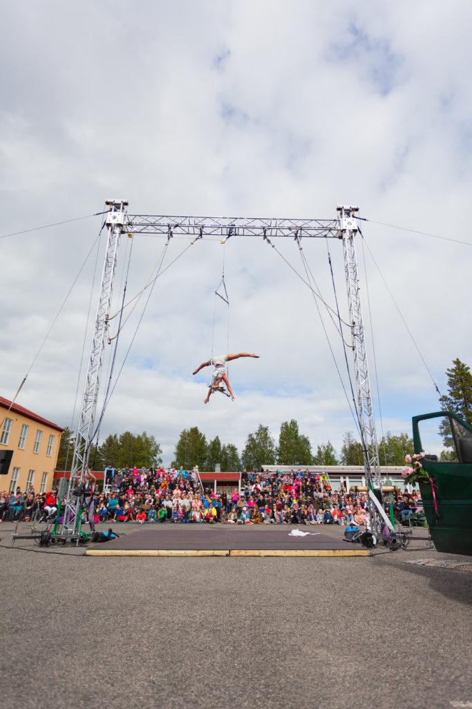 Ammattilainen sirkustaiteilija temppuilee pylvistä roikkuvan