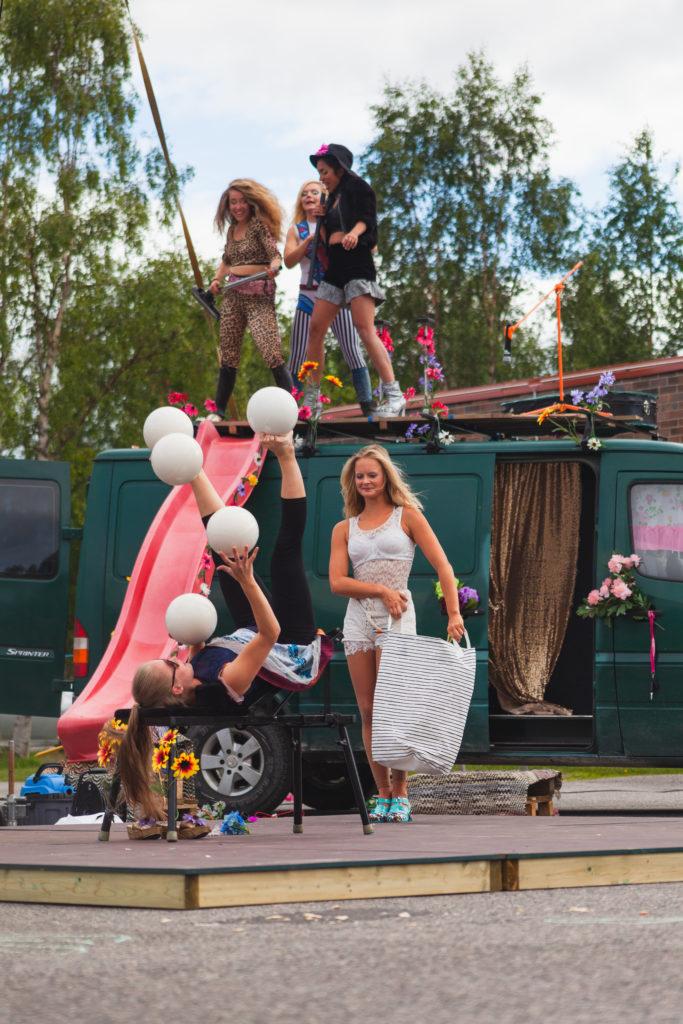 Viisi naista esittää sirkustaidetta vihreän pakettiauton ympärillä. Naisilla on värikkäitä esiintymisasuja. Pakettiauton katolta tulee alas liukumäki. Yksi naisista on selällään ja jongleeraa käsin ja jaloin viidellä pallolla yhtä aikaa.