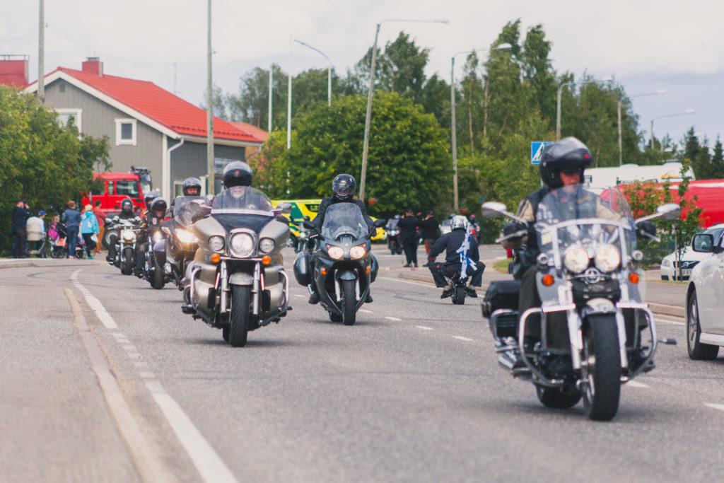 Moottoripyörät ajavat tiellä mustissa kypäröissään Kolarin kirkonkylällä.