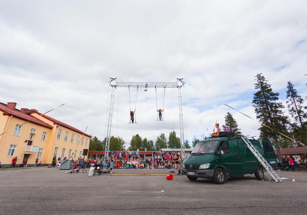 Sirkuksen trapetsitaiteilijat esiintyvät Kolarin lukion pihassa yleisön ihaillessa hurjia keinutemppuja.