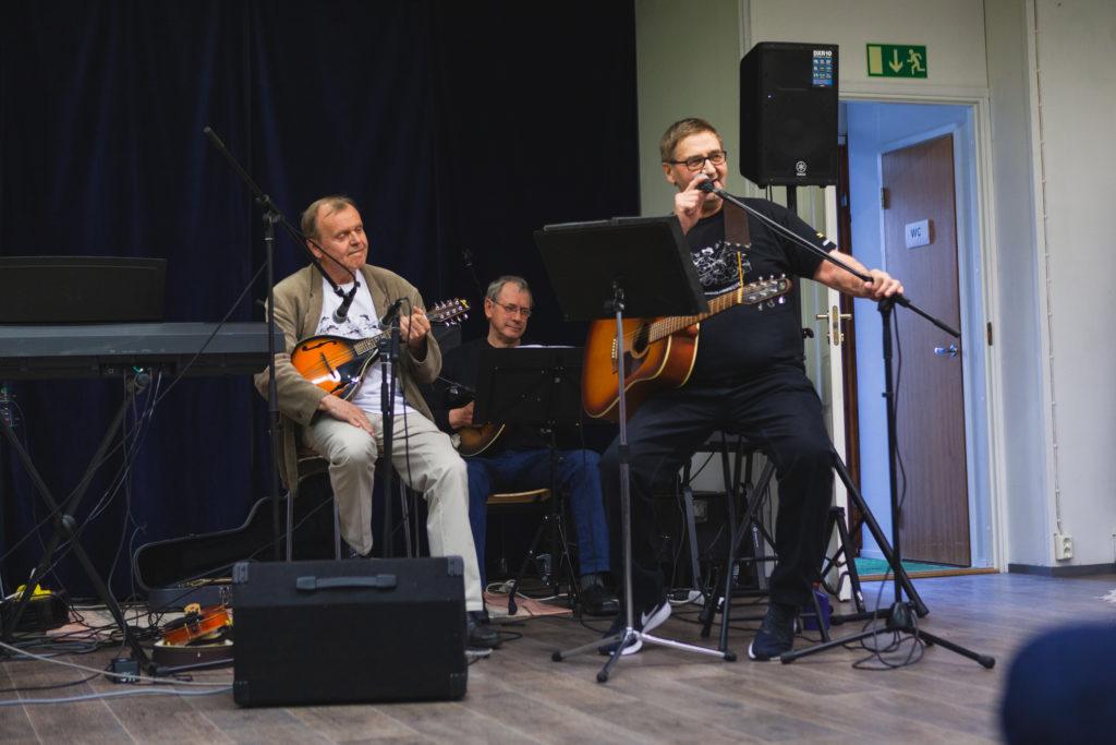Kolme iäkästä miestä esiintyy soittaen.