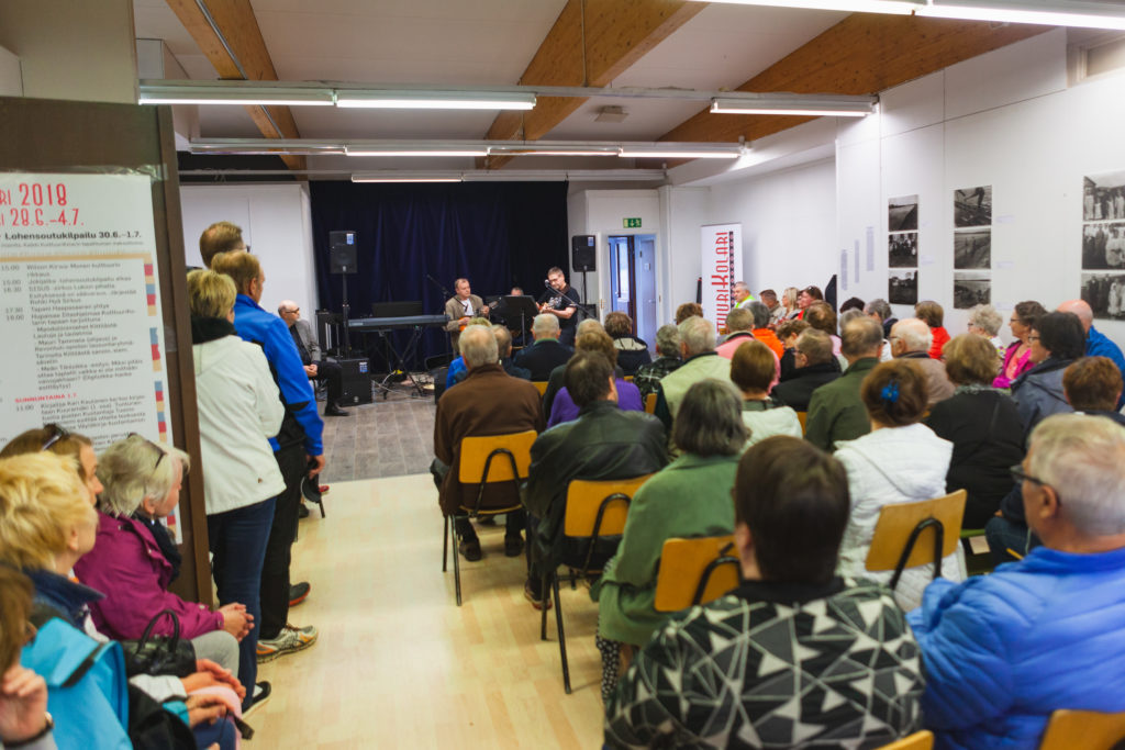 Yleisö seuraa istuen kielisoittimilla soittavaa kittiläläistä senioribändiä.