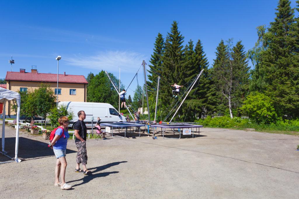 Kaksi lasta pomppii valjaiden varassa kumpikin omilla trampoliineilla.