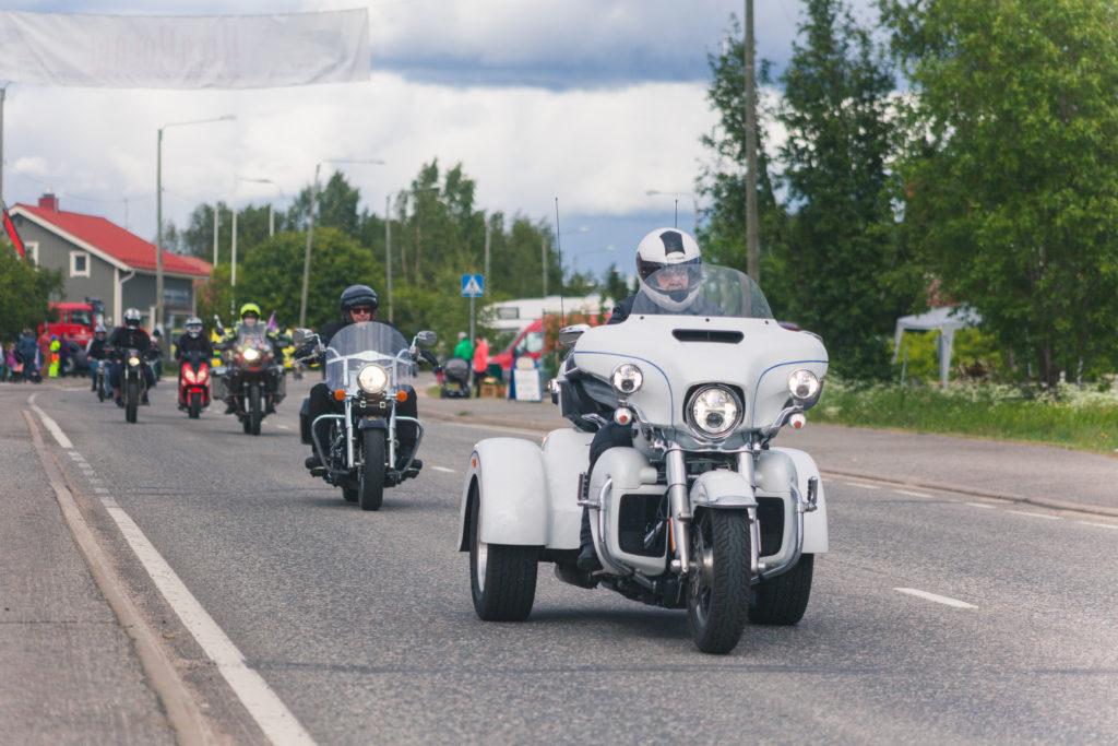 Moottoripyöräkulkue matkalla läpi Kolarin kirkonkylän. Edessä valkoinen, kolmipyöräinen pöristeltävä.