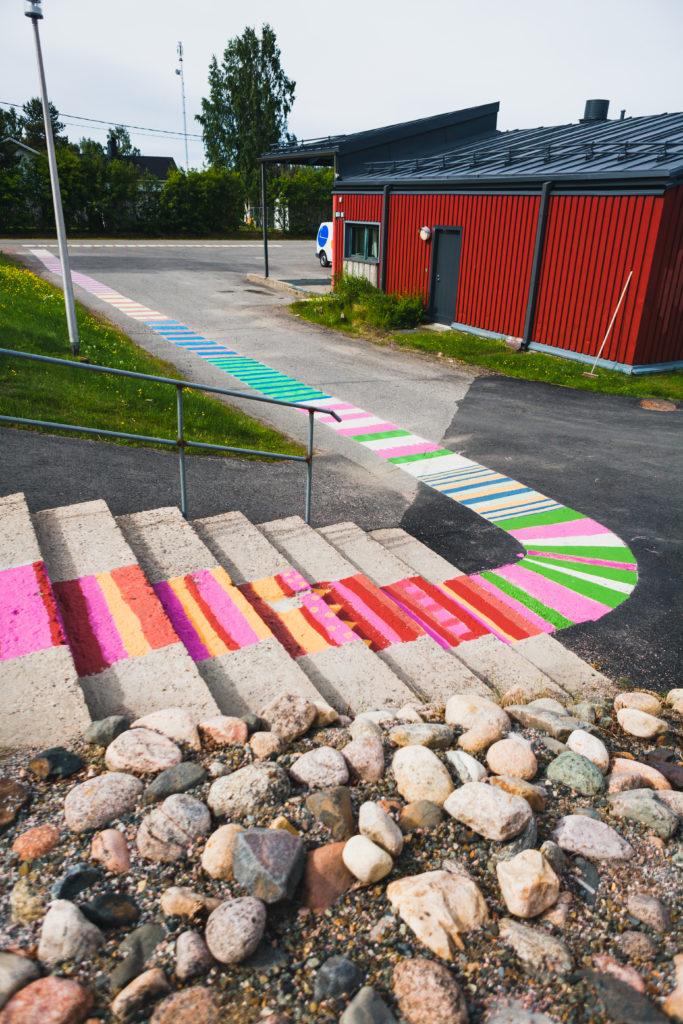 Asfalttiin maalattua mattoa ulottuu Kolarin kirjastoon vieviltä portailta aina päätielle asti usean kymmenen metrin verran.