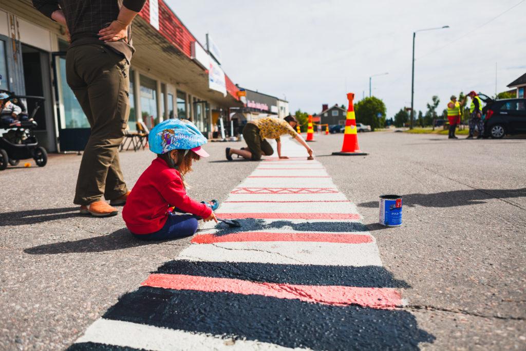 Taapero maalaa asfalttiin tulevaa mattoa sinisellä maalilla kypärä päässään.