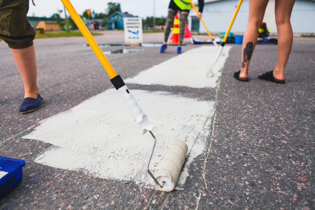 Kolme ihmistä maalaa asfalttiin mattoa valkoisella värillä varsitelalla katutaide-kurssilla Kolarissa.
