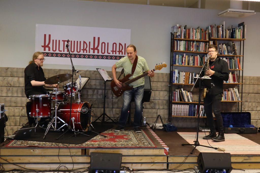 Rumpali. basisti ja saksofonin soittaja ovat lavalla soittamassa. He ovat miehiä. Taustalla on KulttuuriKolari-kyltti ja kirjahylly.