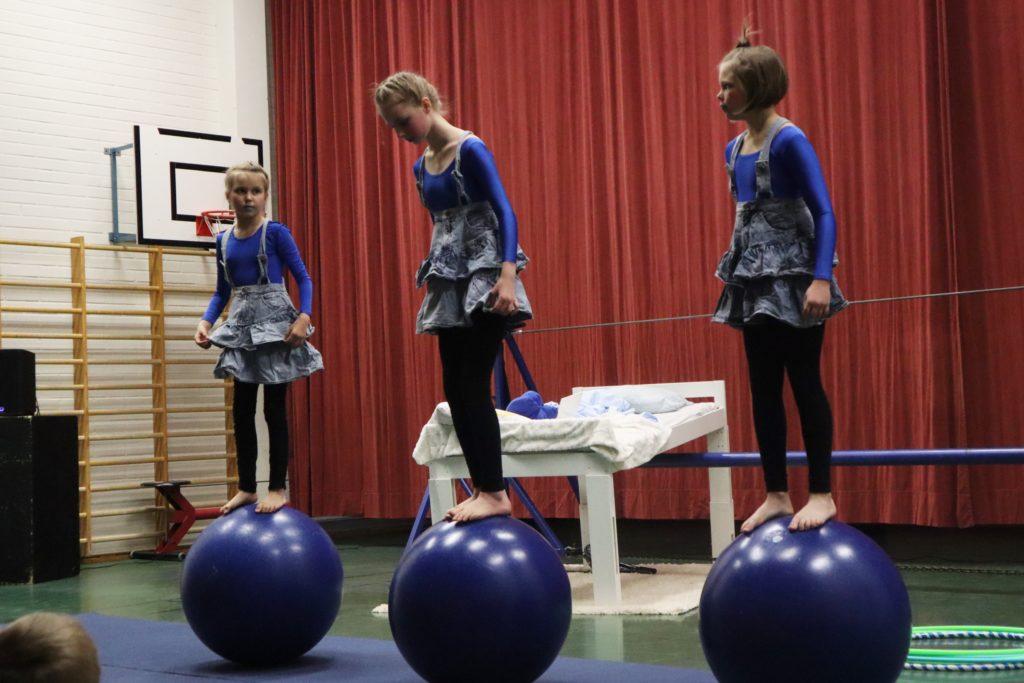 Kolme tyttölasta seisoo sinisillä tasapainopalloilla. Taustalla on punainen esirippu.