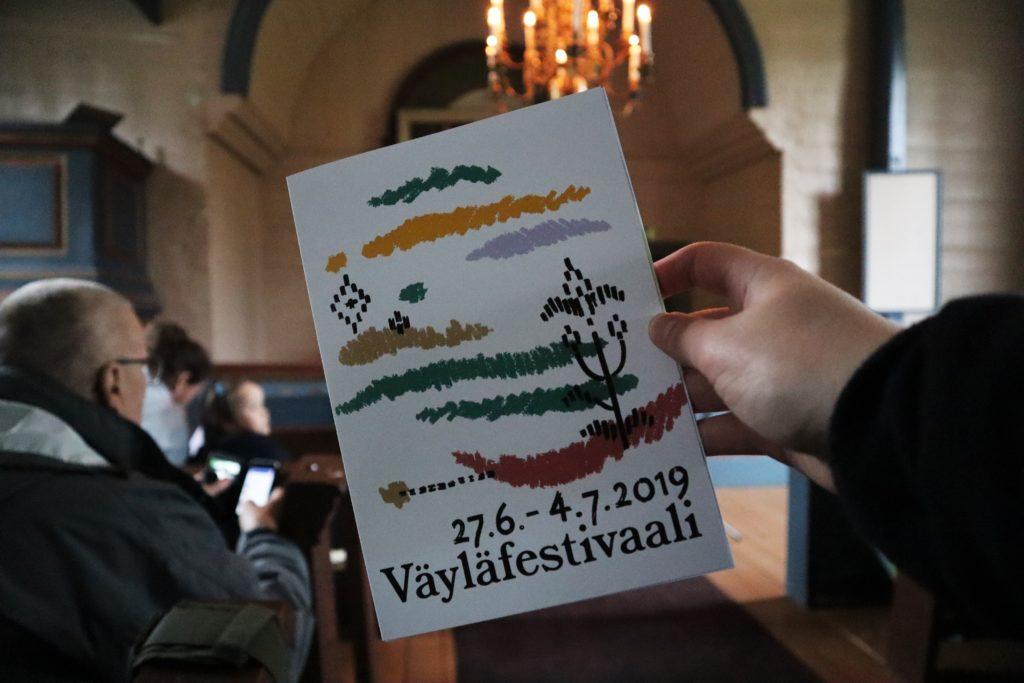 """Kuvassa flyeri, jossa lukee """"Väyläfestivaali"""". Taustalla kirkkonäkymää sisätiloista."""