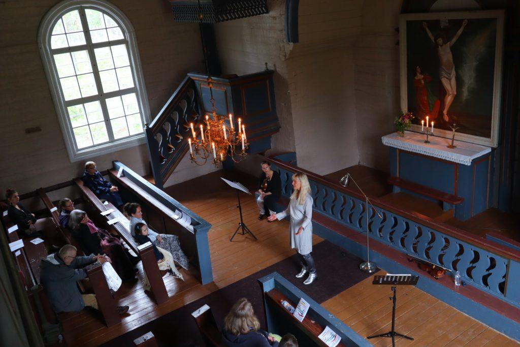 Kirkkonäkymä yläpuolelta. Alttarin edessä kaksi naista esiintyy yleisölle.
