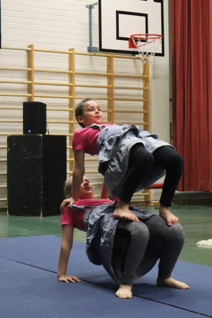Kaksi tyttölasta sirkusasuissa ovat siltakaato -asennossa. Toinen on toisen päällä.