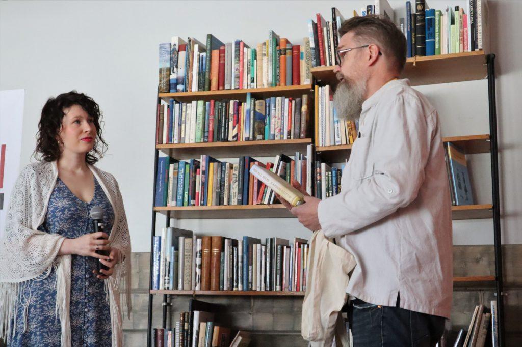 Mies puhuu esiintyjänaiselle kirja ja kassi kädessään. Taustalla on iso kirjahylly täynnä kirjoja.