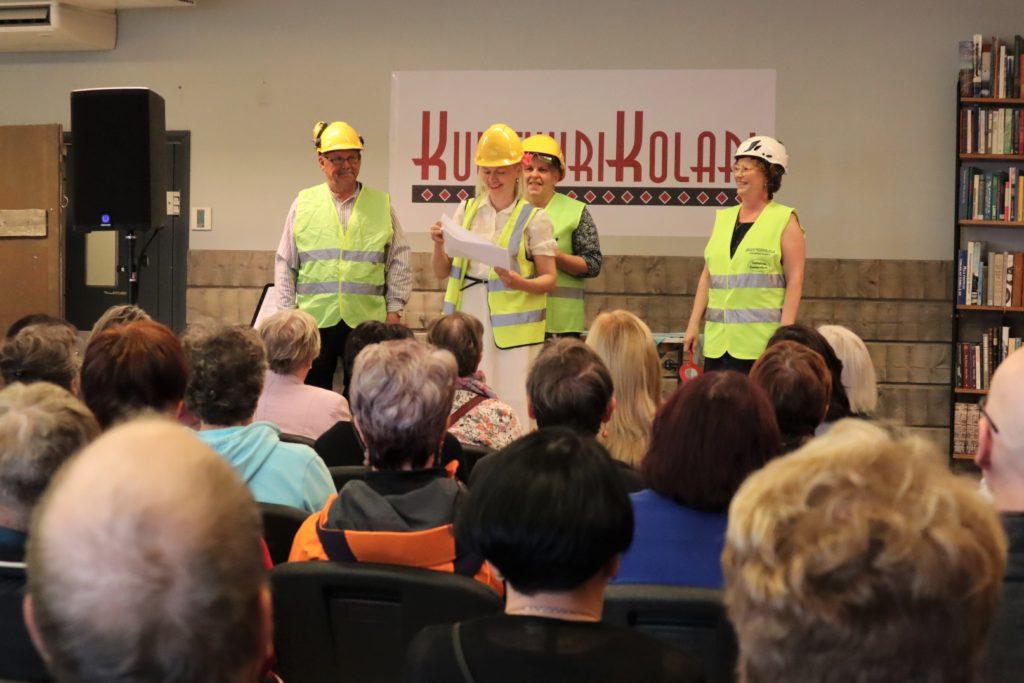 Neljä turvaliiveihin pukeutunutta henkilöä esiintyy lavalla. Yleisö seuraa.