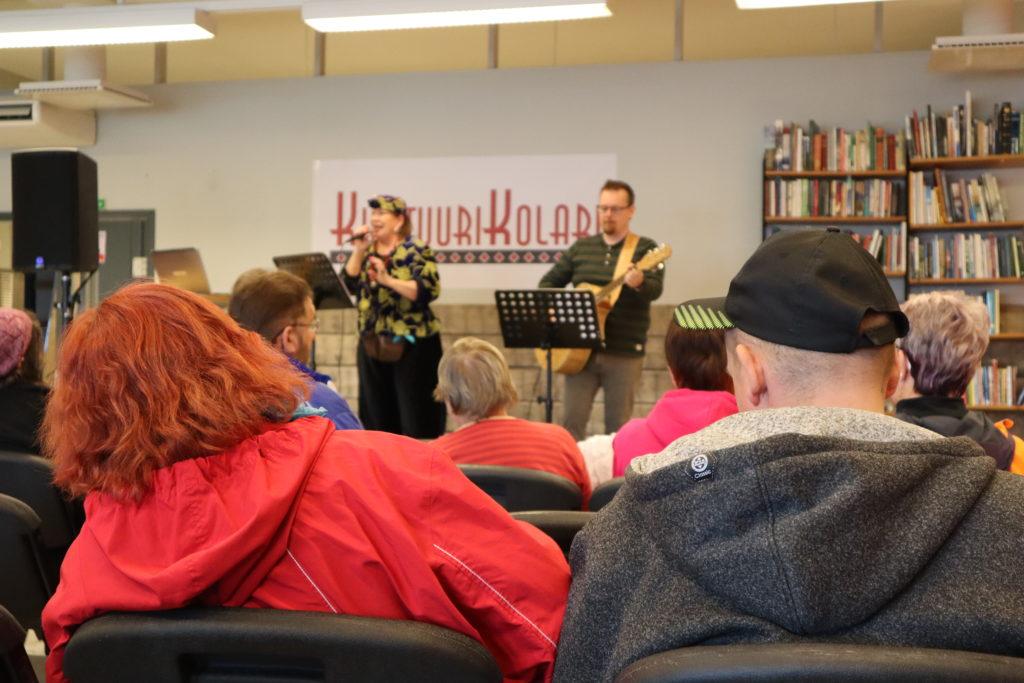Nainen ja mies istuvat yleisössä. Taustalla on sinikeltaiseen asuun pukeutunut, hattupäinen laulajanainen sekä mieskitaristi lavalla.