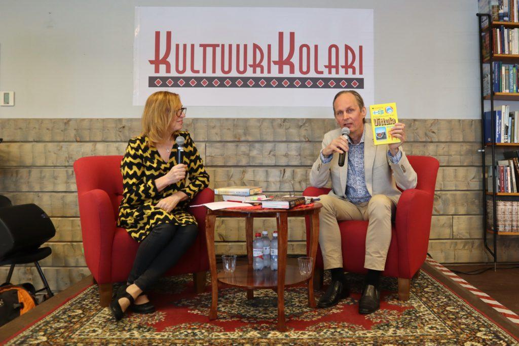 Kirjailija Mikael Niemi pitelee kädessään kirjaansa. Vieressä istuu haastattelija. Heillä molemmilla on mikki kädessään.