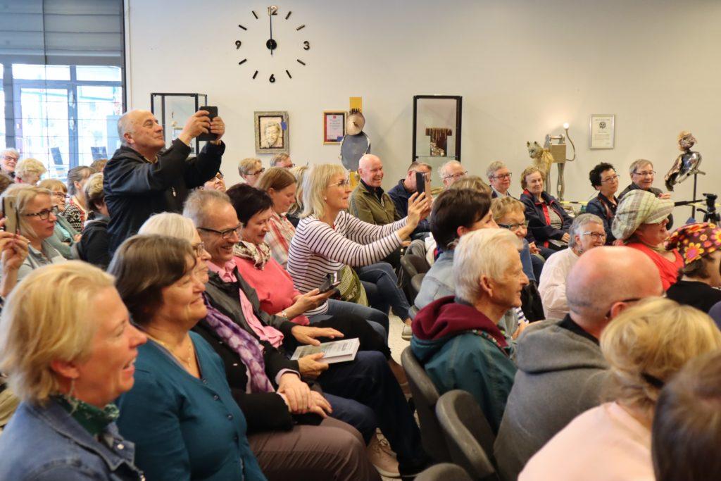 Istuva yleisö kuvaa kännykkäkameroilla esitystä. Osa nauraa.