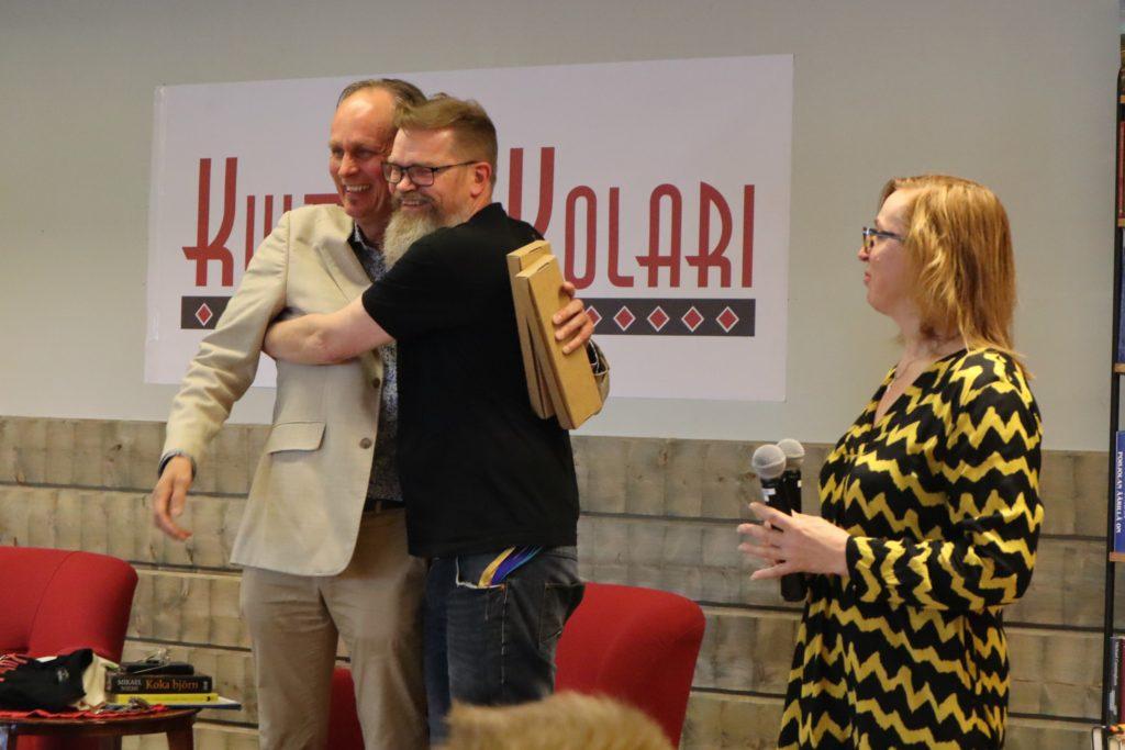 Kaksi miestä halaa toisiaan KulttuuriKolari -kyltin edessä lavalla iloisesti.