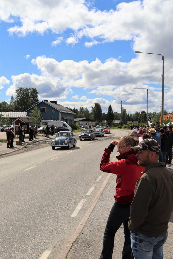 Iso joukko ihmisiä seuraa tienlaidassa, kun vanhat amerikanraudat ajavat ohi.