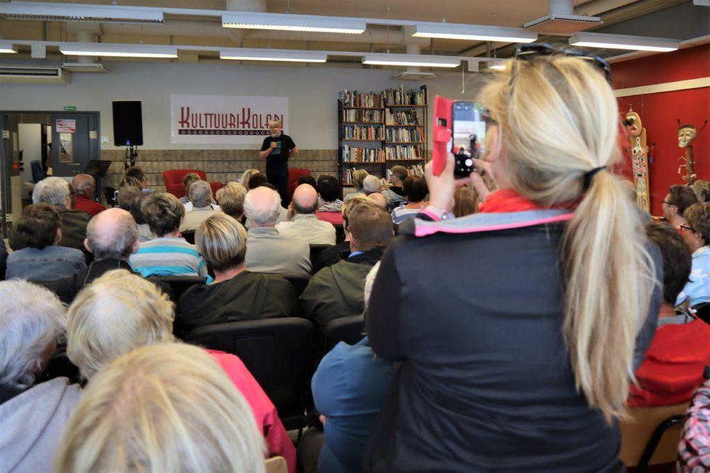 Vaaleahiuksinen nainen ottaa kuvaa yleisön takaosasta esiintyjästä. Taustalla on esiintyjämies, joka puhuu mikkiin lavalla.