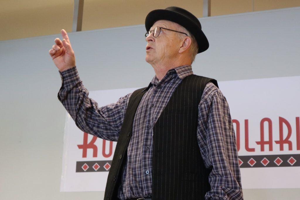 Iäkäs mies elehtii käsillään vanhanaikaisessa asussa hattu päässään. Taustalla on KulttuuriKolari -kyltti.
