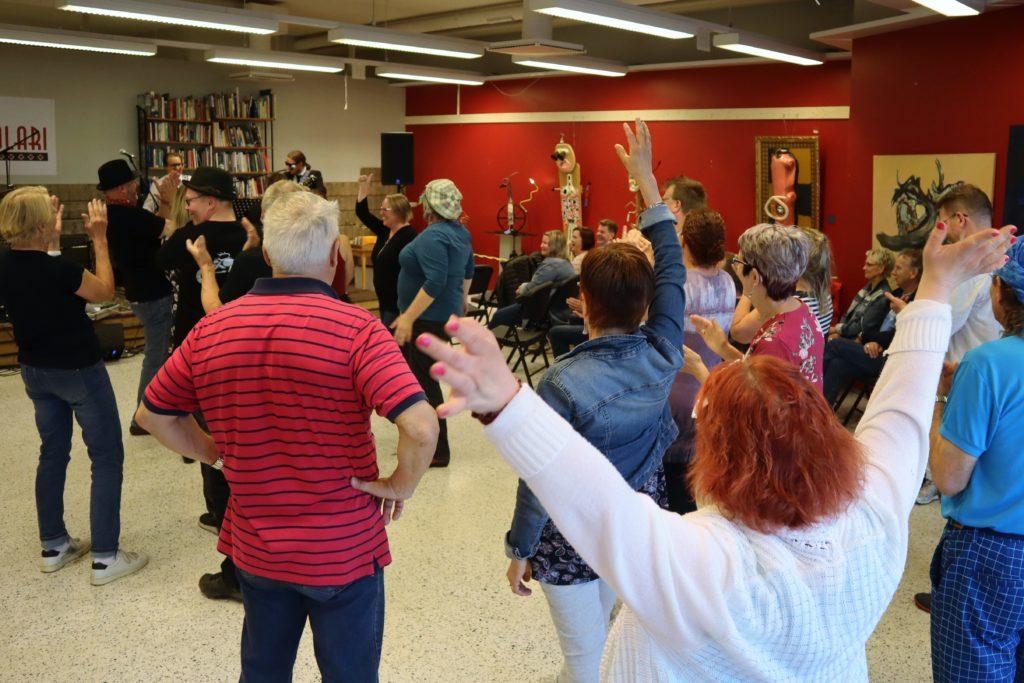 Kuva seisovasta yleisöstä avaralla lattialla. Osa hurraa pitäen käsiä ylhäällään, osa taputtaa,