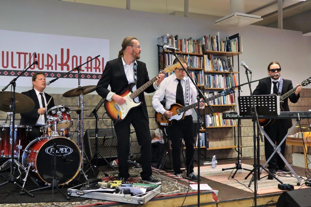 Rumpali, basisti, kitaristi ja kosketinsoittaja lavalla. He ovat noin 30-vuotiaita miehiä ja heillä on puvut päällään.