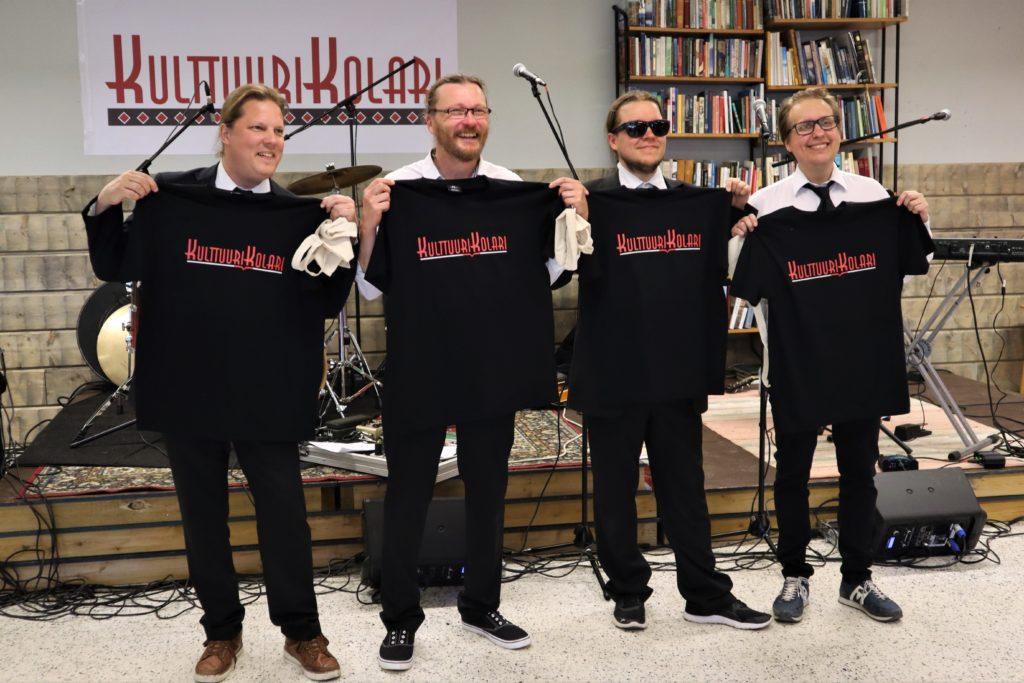 """Neljä esiintyämiestä pitelee edessään mustaa t-paitaa, jossa lukee punaisella """"kulttuurikolari"""". He hymyilevät kauniisti rivissä."""
