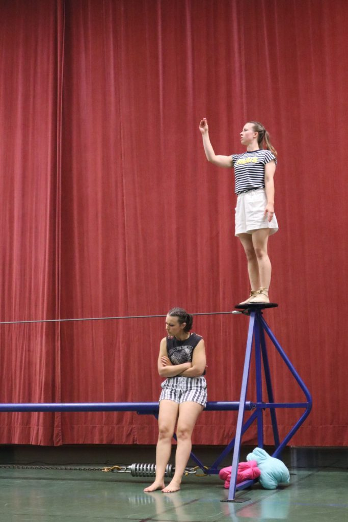 Nuori nainen seisoo trapetsin toisessa päässä pidellen oikeaa kättänsä ylhäällä katse kädessä. Lattiatasossa toinen nainen nojaa trapetsin pylvääseen kädet puuskassa, Takana on punainen esirippu.