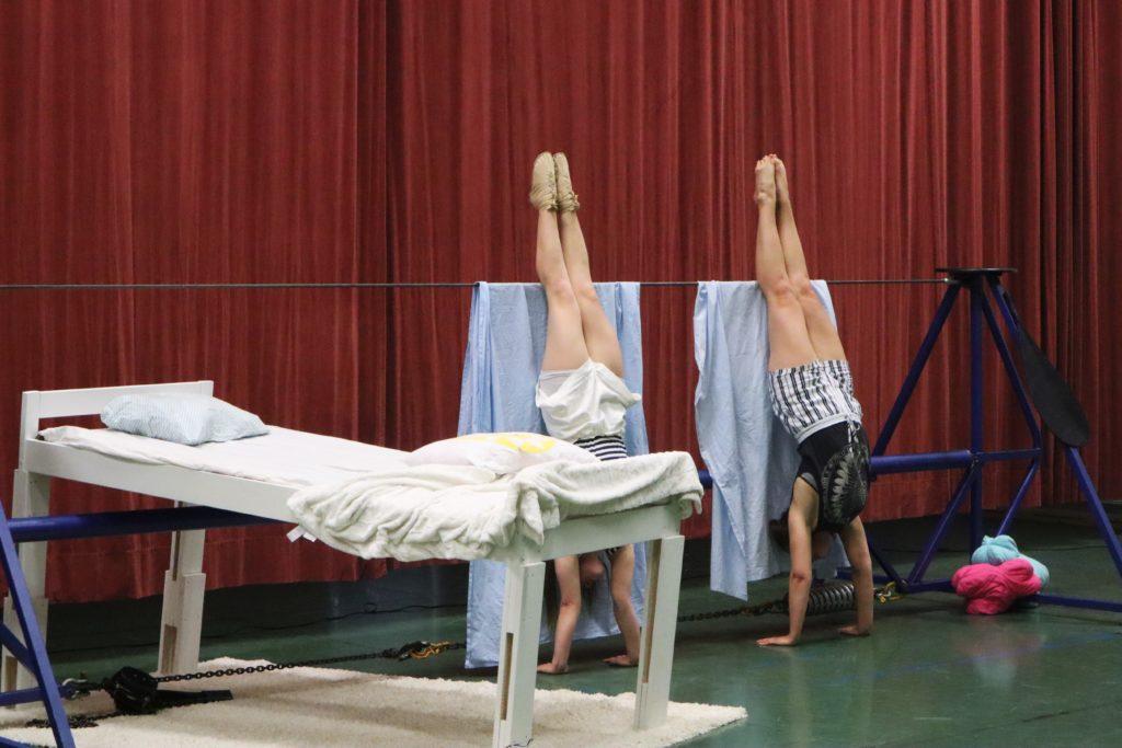 Kaksi nuorta naista seisovat käsillään trapetsista roikkuvia lakanoita vasten.