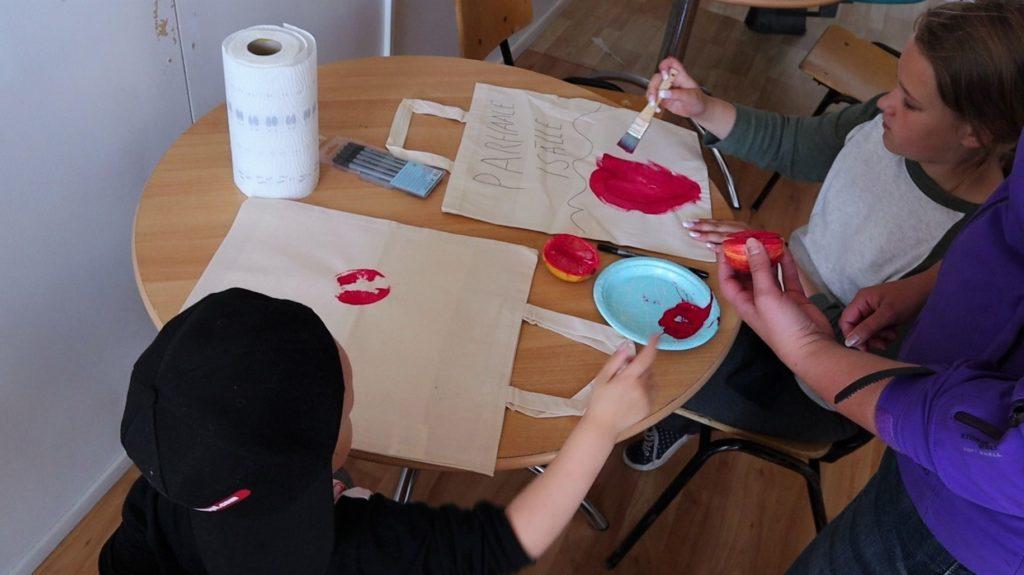 Pieni poika, noin 3-vuotias ja alakouluikäinen tyttö maalaavat luonnonvalkoisia kangaskasseja punaisella värillä pensseleineen. Pöydällä on hedelmä, jossa on maalia painamisen jäljiltä.